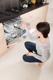Mujer que usa un lavaplatos en una cocina moderna Imagen de archivo