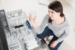 Mujer que usa un lavaplatos en una cocina moderna Fotos de archivo libres de regalías