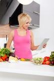 Mujer que usa un ordenador de la tablilla para cocinar Imagenes de archivo