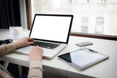 Mujer que usa un ordenador portátil al lado de una ventana Fotos de archivo
