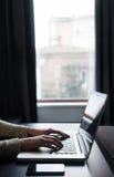 Mujer que usa un ordenador portátil al lado de una ventana con PC y el smartph de la tableta Imagen de archivo