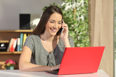 Mujer que usa un ordenador portátil e invitando al teléfono Fotos de archivo libres de regalías