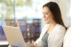 Mujer que usa un ordenador portátil en un apartamento Foto de archivo libre de regalías