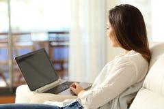 Mujer que usa un ordenador portátil en el apartamento Imagen de archivo