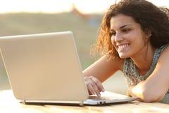 Mujer que usa un ordenador portátil en un parque en la puesta del sol Fotografía de archivo libre de regalías