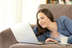 Mujer que usa un ordenador portátil que miente en un sofá en casa Imagen de archivo libre de regalías
