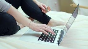 Mujer que usa un ordenador portátil que se sienta en una cama en casa foto de archivo