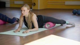 Mujer que usa un rodillo de la espuma en el piso en un gimnasio almacen de video