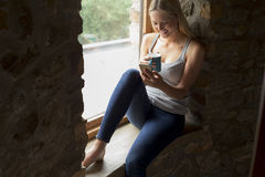 Mujer que usa un smartphone en su hogar Foto de archivo libre de regalías