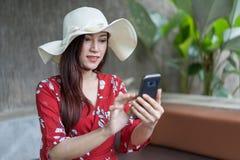 Mujer que usa un smartphone a la red social Imagen de archivo