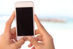Mujer que usa un teléfono elegante Fotografía de archivo libre de regalías