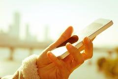 Mujer que usa un teléfono elegante Imagen de archivo libre de regalías
