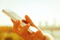 Mujer que usa un teléfono elegante Imágenes de archivo libres de regalías