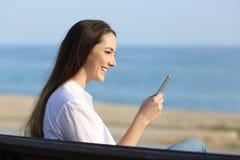 Mujer que usa un teléfono elegante al aire libre en la playa Fotos de archivo
