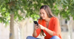 Mujer que usa un teléfono elegante en un banco en un parque