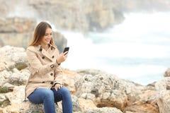Mujer que usa un teléfono elegante en invierno en la playa Imagenes de archivo