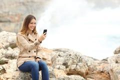 Mujer que usa un teléfono elegante en la playa en invierno Imagen de archivo