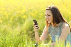 Mujer que usa un teléfono elegante en un campo verde Fotos de archivo libres de regalías