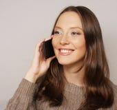 Mujer que usa un teléfono móvil aislado en un fondo blanco Foto de archivo