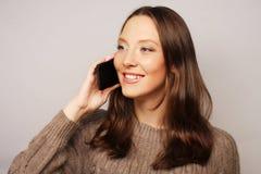Mujer que usa un teléfono móvil aislado en un fondo blanco Imagen de archivo