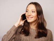 Mujer que usa un teléfono móvil en un fondo blanco Fotografía de archivo libre de regalías