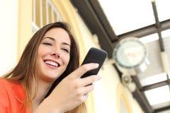 Mujer que usa un teléfono móvil en una estación de tren Imágenes de archivo libres de regalías