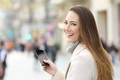 Mujer que usa un teléfono y mirando la cámara en invierno Fotos de archivo
