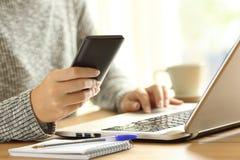 Mujer que usa un teléfono y un ordenador portátil en una tabla Foto de archivo