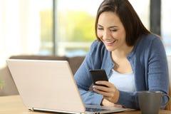 Mujer que usa un teléfono y un ordenador portátil que se sientan en casa Fotos de archivo libres de regalías