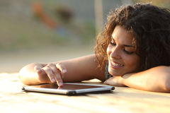 Mujer que usa una pantalla táctil de la tableta en la puesta del sol Foto de archivo