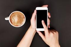 Mujer que usa una pantalla táctil del teléfono elegante Fotografía de archivo libre de regalías