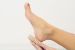 Mujer que usa una piedra de piedra pómez para exfoliate sus pies Imagen de archivo