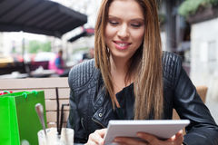 Mujer que usa una tableta digital para relajar sentarse en una silla en un café Imágenes de archivo libres de regalías