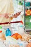 Mujer que usa una tableta en el supermercado fotografía de archivo