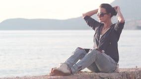 Mujer que usa una tableta en la playa durante puesta del sol metrajes