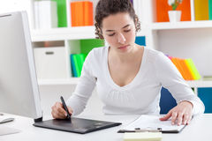 Mujer que usa una tableta gráfica y una pluma Imágenes de archivo libres de regalías