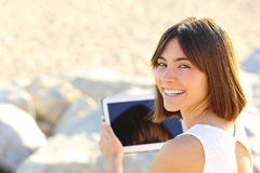 Mujer que usa una tableta y mirando la cámara Imagen de archivo