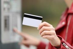 Mujer que usa una tarjeta de crédito para pagar en una máquina del pago foto de archivo libre de regalías