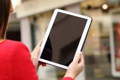 Mujer que usa y mostrando una pantalla en blanco de la tableta Fotos de archivo libres de regalías