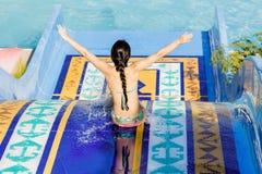 Mujer que va abajo de un tobogán acuático Imagen de archivo