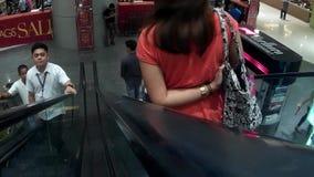 Mujer que va abajo por la escalera móvil en alameda moderna almacen de video