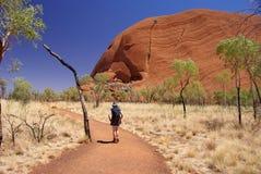 Mujer que va de excursión alrededor de Uluru Imagen de archivo libre de regalías