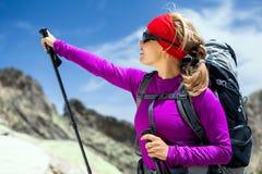 Mujer que va de excursión con el morral en montañas Fotos de archivo libres de regalías