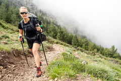 Mujer que va de excursión con el morral en montañas Imagenes de archivo
