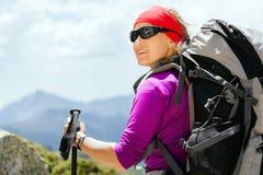 Mujer que va de excursión con el morral en montañas Foto de archivo libre de regalías