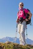 Mujer que va de excursión en altas montañas imagen de archivo