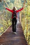 Mujer que va de excursión en puente de suspensión Foto de archivo libre de regalías