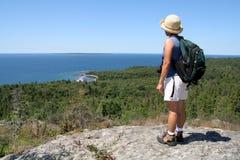 Mujer que va de excursión sobre superior de lago Fotos de archivo