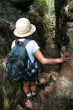 Mujer que va de excursión a través de roca de la fractura Imágenes de archivo libres de regalías