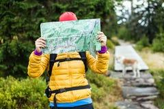 Mujer que va de excursión y que lee la correspondencia en bosque foto de archivo